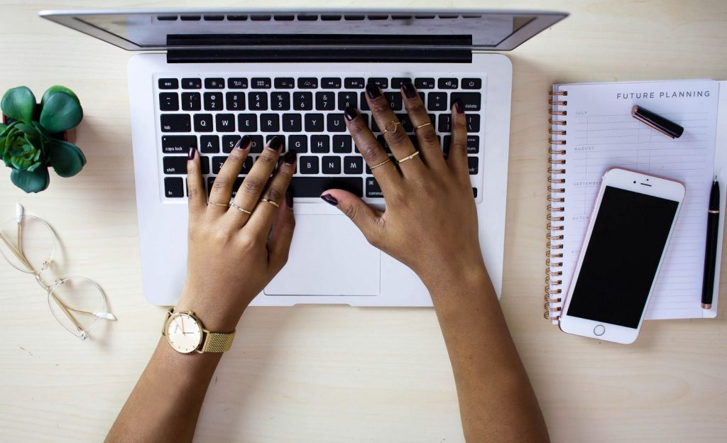 Photo of hands typing on a computer keyboard